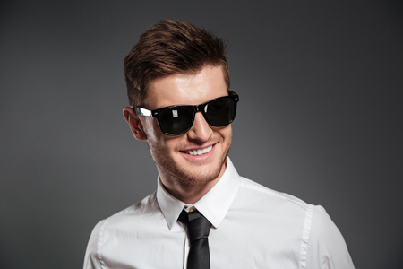 looking aside: Image of cheerful young man dressed in formalwear wearing sunglasses standing isolated over grey wall. Looking aside.