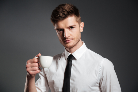 Close up portrait of a handsome young businessman with cup of coffee isolated over grey background