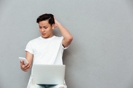Picture of confused young asian man over grey background using laptop computer. Looking at mobile phone.
