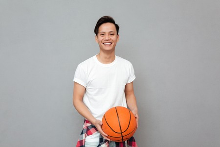 Image of happy young asian man over grey background with basket ball. Looking at camera.
