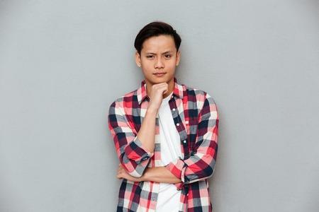 Imagen de hombre joven serio asiático de pie sobre la pared gris. mirando a cámara . Foto de archivo - 80419112