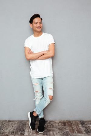 Photo d'un jeune homme asiatique souriant, debout avec les bras croisés sur un mur gris. Regardant de côté. Banque d'images - 80430704