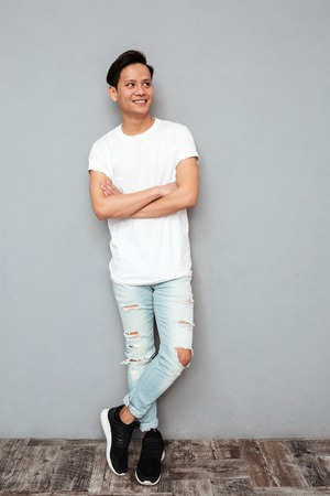 Photo of young smiling asian man standing with arms crossed over grey wall. Looking aside.