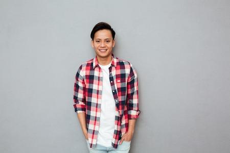 Imagen de joven sonriente hombre asiático de pie sobre la pared gris. mirando a la cámara. Foto de archivo - 80419106