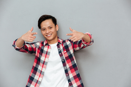 Picture of young cheerful asian man standing over grey wall. Looking at camera and pointing. 版權商用圖片 - 80419100