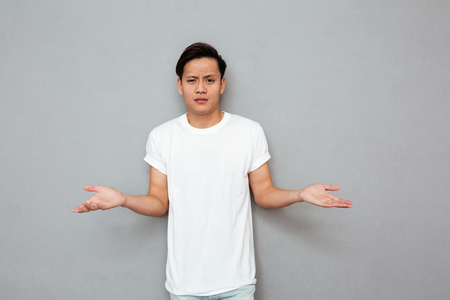 Image of young confused asian man standing over grey wall. Looking at camera.