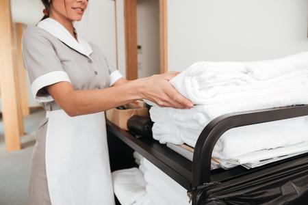Ritagliata immagine di una giovane cameriera sorridente prendendo asciugamani freschi da un carrello di pulizia Archivio Fotografico - 80430896