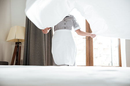 침대 시트를 바꾸는 호텔 하녀의 자른 이미지