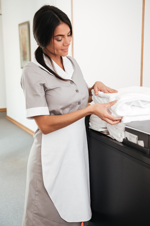Smiling young maid taking fresh towels from a housekeeping cart