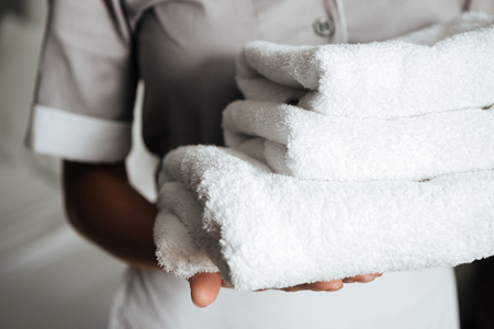 Close up of a young hotel maid holding clean folded towels Фото со стока
