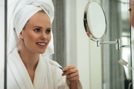 insides: Young blonde woman with towel on head and wearing bathrobe brushing teeth against mirror in bathroom Stock Photo