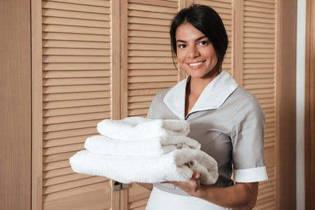 Portrait of a smiling hotel maid holding fresh clean folded towels for the room Banco de Imagens - 80430293
