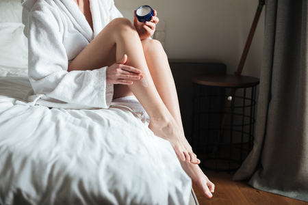 Cropped image of a woman applying moisturizer cream on her leg in bedroom at home