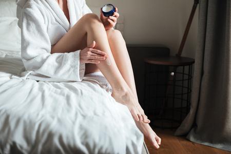 Bebouwd beeld van een vrouw die vochtinbrengende crèmeroom op haar been in slaapkamer thuis toepast