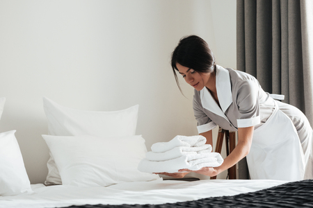 Young hotel maid putting stack of fresh white bath towels on the bed sheet