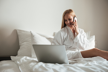Happy pretty woman in bathrobe talking on mobile phone and using laptop while sitting on a bed