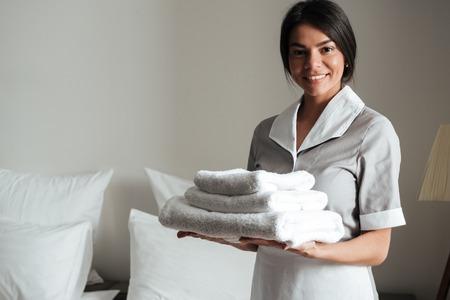 방에 대 한 신선한 깨끗 한 접힌 된 수건을 들고 웃는 호텔 하 녀의 초상화