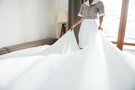 ベッドのシーツを変えるホテルのメイドの画像をトリミング