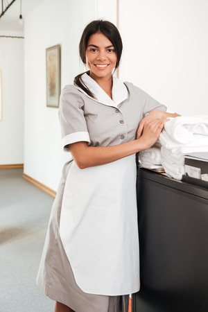 Smiling housekeeping maid standing with bedclothes linen in cart
