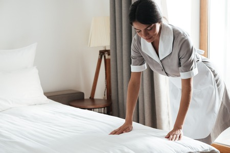 Young hotel maid setting up white bed sheet in hotel room