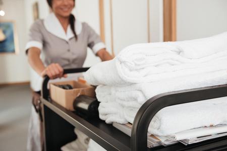 청결한 수건 및 기타 용품을 가져 오는 젊은 호텔 가정부의 자른 이미지
