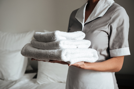 Cropped image of a young hotel maid standing and holding fresh clean towels Stock fotó