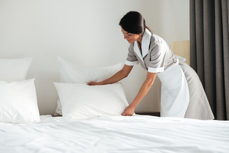 Young hotel maid setting up white pillow on bed sheet in hotel room