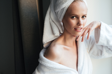 relaxion: Portrait of a beautiful healthy woman in bathrobe and head towel posing and looking at camera indoors