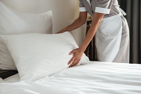 Imagen recortada de una camarera femenina haciendo la cama en la habitación del hotel Foto de archivo - 80452455