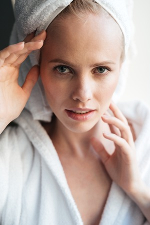 insides: Portrait of beautiful young blonde woman with towel on head looking camera seriously in bathroom