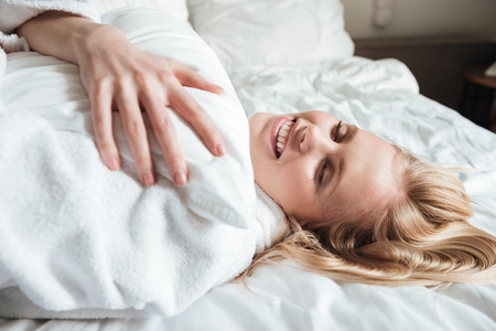 Pretty blonde woman in bathrobe resting on bed at home Imagens