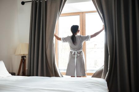 Female housekeeping chambermaid opening window curtains in the hotel room Stok Fotoğraf - 80452753