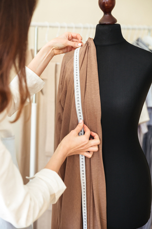 Cropped image of seamstress measuring beautiful fabric on black dummy in workshop