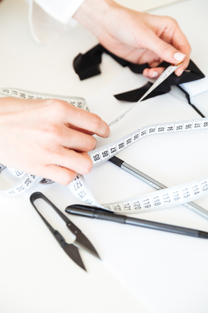 Close up of seamstress working with measuring tape in workshop Stock Photo