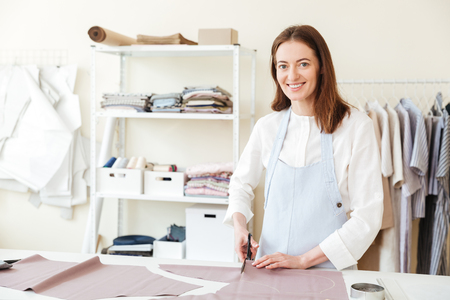 Cheerful woman seamstress using scissors to cut fabric and looking camera in workshop Stock Photo