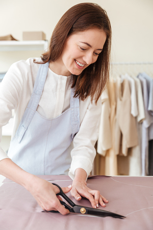 Cheerful woman seamstress using scissors to cut fabric in workshop