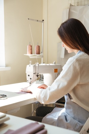 koncentrovaný: Zadní pohled na brunetku švadlena v zástěře pracující se šicí stroj v dílně Reklamní fotografie