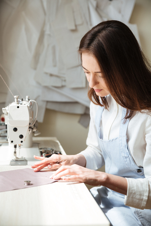 Side view of brunette seamstress in apron working with sewing machine in workshop
