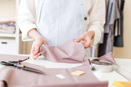 Cropped image of seamstress holding piece of pink fabric in workshop