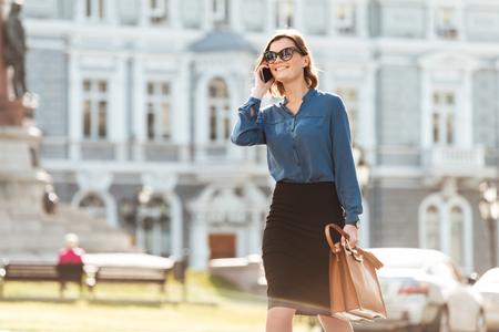 휴대 전화와 가방과 도시 거리에 산책 쾌활한 젊은 여자의 초상화 스톡 콘텐츠 - 80439638