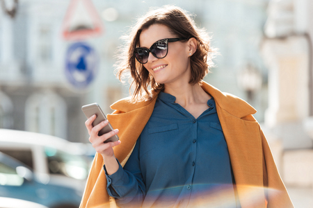 Smiling casual woman in sunglasses looking at mobile phone while standing on a city street
