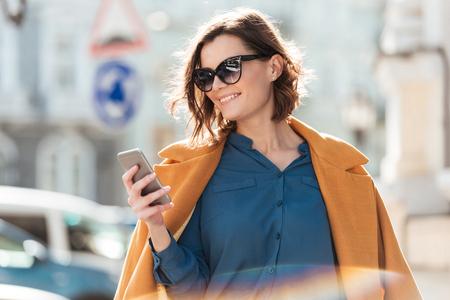Sonriente mujer casual en gafas de sol mirando teléfono móvil mientras está de pie en una calle de la ciudad