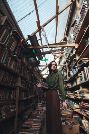 looking aside: Serious girl wearing casual standing in library between shelves with books. Looking aside