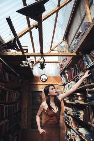 warehouse: Portrait of a stylish woman in dress taking book from a shelf in a warehouse