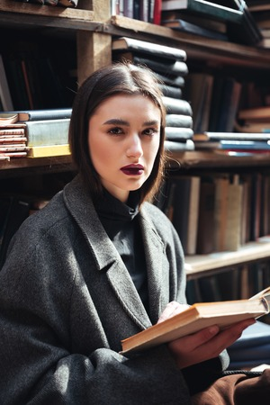 warehouse: Portrait of a beautiful young girl in coat holding book in an old library