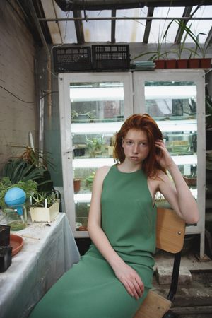 Redhead beautiful girl in green dress gazing at camera in greenery against fridges with plants