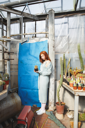 Full length portrait of a young redheaded woman in dress holding a cactus in a glass house