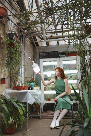 Redhead pensive girl sitting near table in greenery and looking at lamp