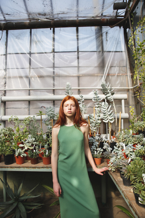 Portrait of an attractive redheaded girl standing in a glass house and looking at camera