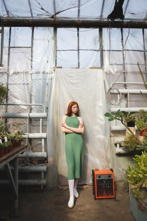 Full length portrait of a young redheaded woman in dress standing and posing in a glass house Stock Photo